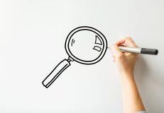Κλείστε επάνω του γραψίματος χεριών πιό magnifier στο λευκό πίνακα Στοκ εικόνα με δικαίωμα ελεύθερης χρήσης