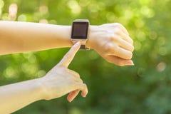 Κλείστε επάνω του δείκτη που πιέζει το κουμπί στο έξυπνο ρολόι Στοκ Φωτογραφία