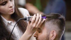 Κλείστε επάνω του επαγγελματικού θηλυκού hairstylist που ντύνεται στα περιστασιακά ενδύματα εξυπηρετεί τον πελάτη σε χρησιμοποίησ φιλμ μικρού μήκους