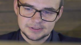Κλείστε επάνω του επιχειρησιακού ανθρώπινου προσώπου που χαμογελά και που κοιτάζει στο lap-top αργά απόθεμα βίντεο