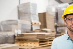 Κλείστε επάνω του εργαζομένου που φορά το σκληρό καπέλο στην αποθήκη εμπορευμάτων Στοκ Εικόνα