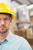 Κλείστε επάνω του εργαζομένου που φορά το σκληρό καπέλο στην αποθήκη εμπορευμάτων Στοκ Φωτογραφία