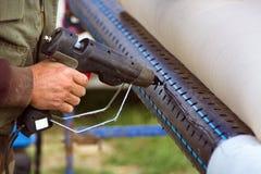 Κλείστε επάνω του εργαζομένου χρησιμοποιώντας το καυτό πλαστικό πυροβόλο όπλο κόλλας στο σωλήνα Στοκ Εικόνες