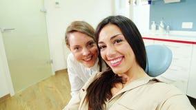 Κλείστε επάνω του ευτυχούς θηλυκού ασθενή με τον οδοντίατρο απόθεμα βίντεο