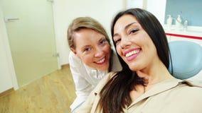 Κλείστε επάνω του ευτυχούς θηλυκού ασθενή με τον οδοντίατρο φιλμ μικρού μήκους