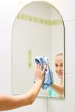 Κλείστε επάνω του ευτυχούς καθαρίζοντας καθρέφτη γυναικών με το κουρέλι στοκ εικόνα