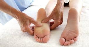 Κλείστε επάνω του θεράποντος που τρίβει τα πόδια του ασθενή της απόθεμα βίντεο