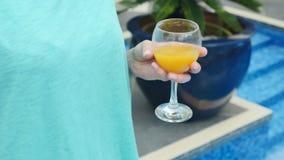 Κλείστε επάνω του θηλυκού ποτηριού εκμετάλλευσης χεριών του χυμού από πορτοκάλι κοντά στην πισίνα απόθεμα βίντεο