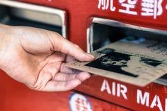Κλείστε επάνω του θηλυκού χεριού βάζοντας το φάκελο στην ταχυδρομική θυρίδα Στοκ φωτογραφία με δικαίωμα ελεύθερης χρήσης