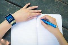 Κλείστε επάνω του θηλυκού χεριού που παίρνει τις σημειώσεις και που φορά το έξυπνο ρολόι Στοκ Φωτογραφίες