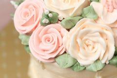 Κλείστε επάνω του κέικ γάμου ή γενεθλίων που διακοσμείται τα λουλούδια που γίνονται με από την κρέμα Στοκ Εικόνες