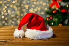 Κλείστε επάνω του καπέλου santa στον ξύλινο πίνακα πέρα από τα φω'τα Στοκ Εικόνα
