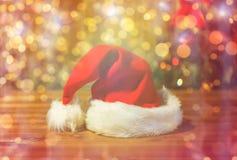 Κλείστε επάνω του καπέλου santa στον ξύλινο πίνακα πέρα από τα φω'τα Στοκ εικόνα με δικαίωμα ελεύθερης χρήσης