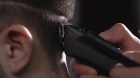 Κλείστε επάνω του κεφαλιού του νεαρού άνδρα που παίρνει το κούρεμα από τον κομμωτή στο μοντέρνο barbershop Εικόνα της θηλυκής χρη απόθεμα βίντεο