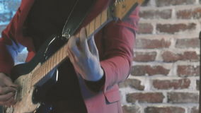 Κλείστε επάνω του κιθαρίστα τζαζ στο σκηνικό παιχνίδι σε electroguitar με το μεσολαβητή μπροστά από το τουβλότοιχο, εκλεκτής ποιό απόθεμα βίντεο