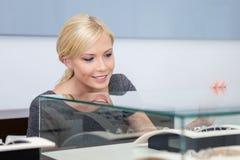 Κλείστε επάνω του κοριτσιού που εξετάζει το κόσμημα σε περίπτωση γυαλιού Στοκ φωτογραφία με δικαίωμα ελεύθερης χρήσης