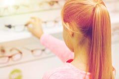 Κλείστε επάνω του κοριτσιού που επιλέγει τα γυαλιά στο κατάστημα οπτικής Στοκ Εικόνα