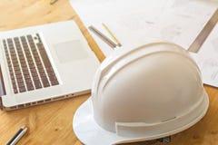 Κλείστε επάνω του κράνους με τον αρχιτέκτονα που σκιαγραφεί ένα κατασκευαστικό πρόγραμμα στοκ φωτογραφίες