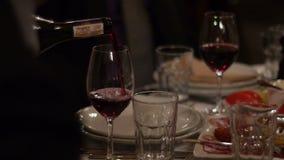 Κλείστε επάνω του κρασιού που χύνεται στο γυαλί που απομονώνεται σε έναν πίνακα γευμάτων απόθεμα βίντεο