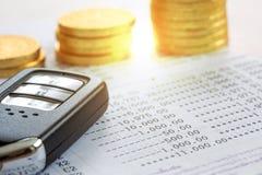 Κλείστε επάνω του κλειδιού αυτοκινήτων με τα νομίσματα στο βιβλιάριο για τα χρήματα δανείου στην έννοια αυτοκινήτων Στοκ φωτογραφίες με δικαίωμα ελεύθερης χρήσης