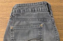 Κλείστε επάνω του μαύρου τζιν Jean στον ξύλινο πίνακα Στοκ φωτογραφία με δικαίωμα ελεύθερης χρήσης