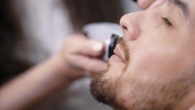 Κλείστε επάνω του νέου γενειοφόρου ατόμου που παίρνει το κούρεμα στο πρόσωπό του από τον κομμωτή στο μοντέρνο barbershop θηλυκή ε απόθεμα βίντεο