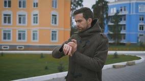 Κλείστε επάνω του νέου γενειοφόρου ατόμου στο καφετί παλτό που περπατά στην οδό κοντά στα κτήρια και που ελέγχει το ρολόι του Το  απόθεμα βίντεο