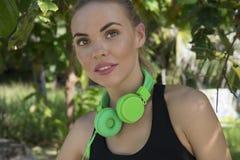 Κλείστε επάνω του νέου όμορφου θηλυκού ικανότητας που φορά τα βεραμάν ακουστικά που χαμογελούν και που εξετάζουν τη κάμερα στην π στοκ φωτογραφία