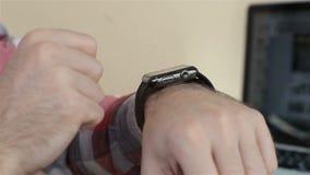 Κλείστε επάνω του νεαρού άνδρα χρησιμοποιώντας smartwatch καθμένος στον καφέ φιλμ μικρού μήκους