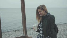 Κλείστε επάνω του ξανθού όμορφου καφέ κατανάλωσης γυναικών και κοίταγμα στη θάλασσα απόθεμα βίντεο