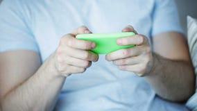Κλείστε επάνω του παίζοντας παιχνιδιού ατόμων στο smartphone στο σπίτι απόθεμα βίντεο