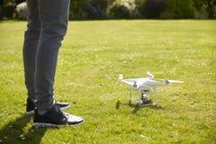 Κλείστε επάνω του πετώντας κηφήνα Quadcopter ατόμων στον κήπο Στοκ Εικόνα