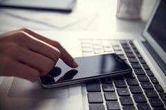 Κλείστε επάνω του προσώπου στο lap-top χρησιμοποιώντας το κινητό τηλέφωνο Στοκ Εικόνες