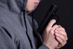 Κλείστε επάνω του πυροβόλου όπλου στο αρσενικό παραδίδει το γκρι Στοκ φωτογραφία με δικαίωμα ελεύθερης χρήσης