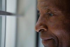 Κλείστε επάνω του στοχαστικού ανώτερου ατόμου που κοιτάζει έξω μέσω του παραθύρου Στοκ εικόνα με δικαίωμα ελεύθερης χρήσης