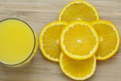 Κλείστε επάνω του τεμαχισμένου πορτοκαλιού και ενός πλήρους ποτηριού του χυμού από πορτοκάλι στην ξύλινη επιφάνεια στοκ εικόνες