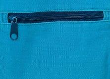 Κλείστε επάνω του φερμουάρ στο μπλε υπόβαθρο τσαντών Στοκ Φωτογραφίες