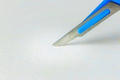 Κλείστε επάνω του χειρουργικού νυστεριού ενάντια στην άσπρη επιφάνεια Στοκ Εικόνες