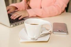 Κλείστε επάνω του χεριού επιχειρηματιών που λειτουργεί και που κρατά με ένα χέρι ένα φλυτζάνι του coffe χρυσή ιδιοκτησία βασικών  Στοκ εικόνα με δικαίωμα ελεύθερης χρήσης