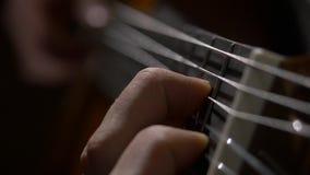 Κλείστε επάνω του χεριού κιθαριστών παίζοντας την ακουστική κιθάρα Κλείστε αυξημένος ενός ατόμου με τα δάχτυλά του στους μαιάνδρο απόθεμα βίντεο