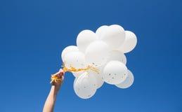 Κλείστε επάνω του χεριού με τα άσπρα μπαλόνια στο μπλε ουρανό Στοκ εικόνες με δικαίωμα ελεύθερης χρήσης