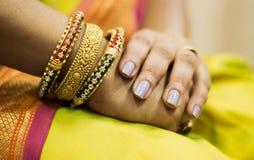 Κλείστε επάνω του χεριού με τα χρυσά βραχιόλια Στοκ εικόνα με δικαίωμα ελεύθερης χρήσης