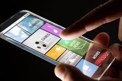 Κλείστε επάνω του χεριού με τα apps στο smartphone Στοκ Φωτογραφία
