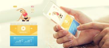 Κλείστε επάνω του χεριού με τον αθλητισμό app στο smartphone Στοκ Φωτογραφίες