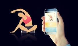 Κλείστε επάνω του χεριού με το smartphone και τον αθλητισμό app Στοκ φωτογραφία με δικαίωμα ελεύθερης χρήσης