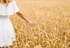 Κλείστε επάνω του χεριού μιας γυναίκας σχετικά με τη χρυσή σίκαλη στοκ εικόνα