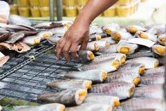 Κλείστε επάνω του χεριού που παίρνει τα ψάρια στην αγορά οδών Στοκ εικόνα με δικαίωμα ελεύθερης χρήσης