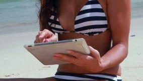 Κλείστε επάνω του όμορφου brunette χρησιμοποιώντας το PC ταμπλετών στην παραλία απόθεμα βίντεο