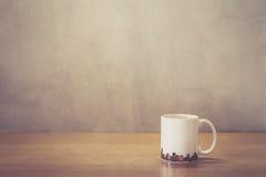 Κλείστε επάνω το άσπρο φλυτζάνι καφέ στον ξύλινο πίνακα Στοκ εικόνες με δικαίωμα ελεύθερης χρήσης