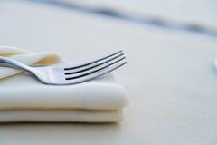 Κλείστε επάνω το δίκρανο στην άσπρη πετσέτα στο εστιατόριο στοκ εικόνες